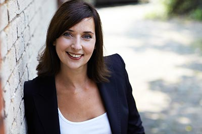 Portrait-Foto von Jeanette Deloch Team- und Führungskräfteentwicklung lächelnd an eine Backsteinmauer gelehnt im Hintergrund ein sonniger Weg